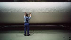 Työmies selkä kameraan päin paperitehtaalla.