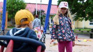 En flicka gungar ett mindre barn som har gul keps på sig på Hulta dagisgård.