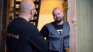 Två medelålders män talar med varandra intill ett hus i fabrikshallen.