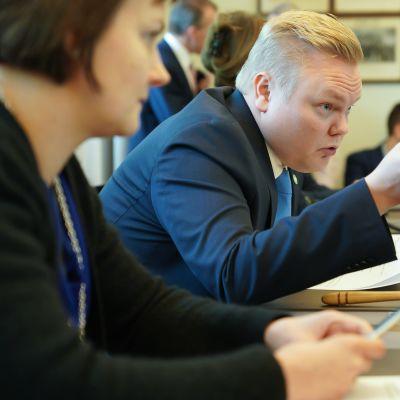 En man pekar mot någonting under ett möte. I bakgrunden syns människor som sitter vid mötesbordet och en mötesklubba.
