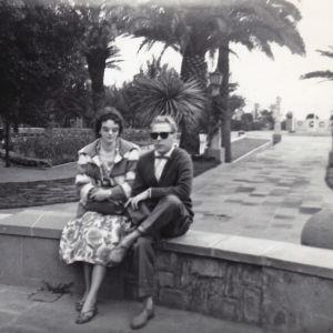 Mustavalkoisessa kuvassa tyylikäs pariskunta istuu kiviaidalla italialaisessa puutarhassa meren rannalla.