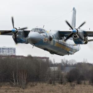 Ett Antonov An-26 flygplan som är mitt i en landning. Planet är ett propellerplan.