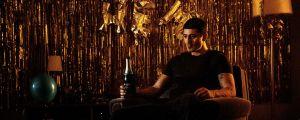 """Teddy (Alexej Manvelov) istuu nojatuolissa ja katsoo mietteliäänä eteensä. Taustalla on kultaisen värisiä koristekirjaimia, joilla on kirjoitettu teksti """"välkommen hem""""."""
