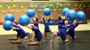 En grupp gymnaster med bollar i händerna knäböjer på scen.