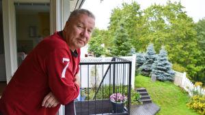En man i röd tröja lutar sig över ett balkongräcke och tittar in i kameran.