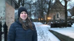 Anne-Maj Åberg står vid porten till kyrkan i Nagu