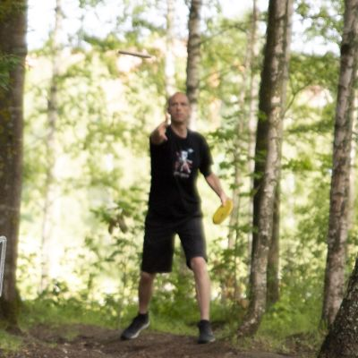 Mies puttaa frisbeegolf-kiekkoa