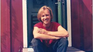 Musikern Micke Allén sitter på en trappa som ung och röker.
