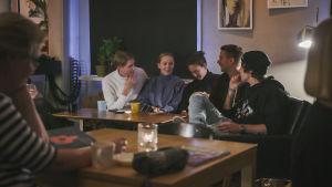 Fem unga personer sitter i en soffa på ett kafé och pratar.