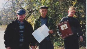 Tre män står utomhus och håller i papper tittar in i kameran. De här männen åkte runt i Vitryssland och hjälpte människor att rösta.