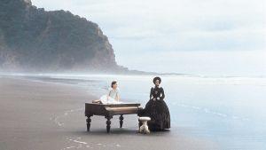 Nainen ja tyttö ja piano autiolla rannalla. Kuva elokuvasta Piano.