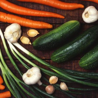 Morötter, purjolök, zucchini och vitlök på ett bord.