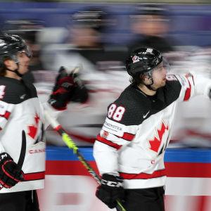 Två kanadensiska spelare skrinnar förbi spelarbåset och firar ett mål.