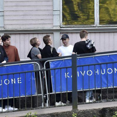 Ungdomar köar utanför Kaivohuone i Brunnsparken i Helsingfors.