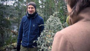 Panu kunttu diskuterar med ritva kovalainen i skogen. Lillträsket skymtar bakom träden i bakgrunden.