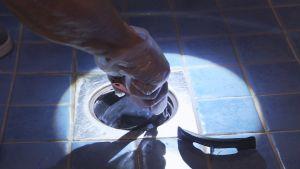 Kuntotarkastaja tutkii lattiakaivoa.
