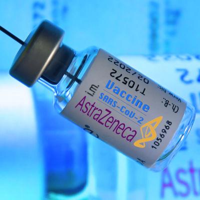 En person håller i en dos med AstraZenecas coronavaccin. I bakgrunden syns fler doser.