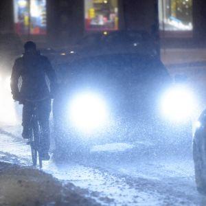 En cyklist och bilar i snöstorm.