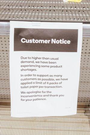En lapp vid en tom butikshylla där det står att man endast får köpa fyra paket toalettpapper.