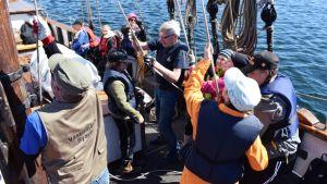 Skolelever hjälper till att reva segel på Eugenias däck.