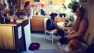 Cecilia Weckström med en av de andra inneboende i kollektivets kök. En katt ligger på soffan och vilar.