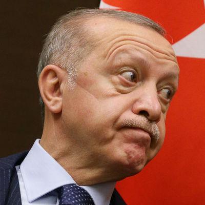 Recep Tayyip Erdoğan tittar åt sidan och gör en grimas, han ser besviken ut – mungiporna pekar neråt. I bakgrunden syns Turkiets flagga.