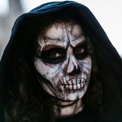 Meikattu ja mustaan huppuun pukeutunut nainen esittää kuolemaa.