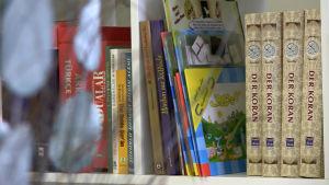 Tyskspråkiga Koranen och andra böcker i en bokhylla.