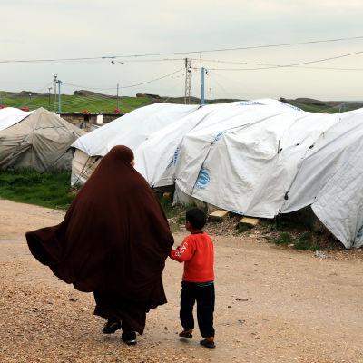 Hustru till en misstänkt IS-krigare promenerar med sin son på ett flyktingläger i Syrien.