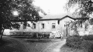 En svartvit bild av människor framför en avlång byggnad