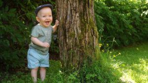 Oliver på sin 1-årsdag. Står vid ett träd.