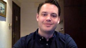 Thomas Nyman, en man med mörkt hår och blå skjorta, sitter hemma och tittar in i kameran. I bakgrunden finns en ljus tavla på väggen.