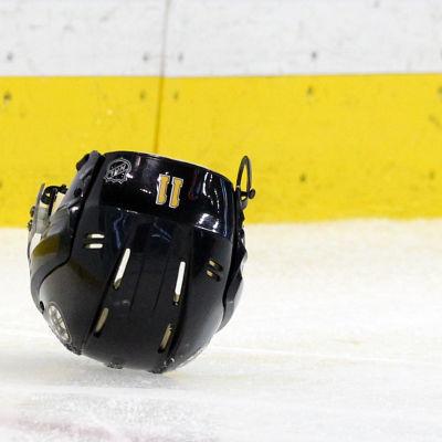 En ishockeyhjälm ligger på isen.