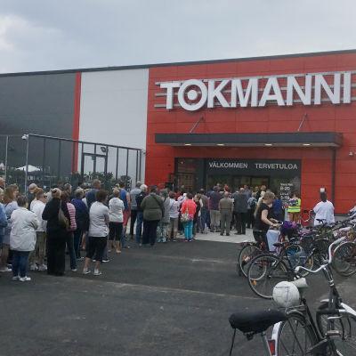 Människor står i kö utanför en butik som snart ska öppna för första gången.