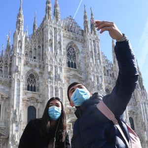 Två personer i munskydd tar en selfie utanför katedralen i Milan.
