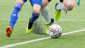 Gummigranulat flyger i luften under fotbollsmatch.