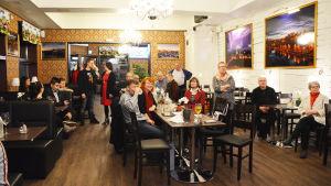 Flera personer i en restaurang runt ett långt bord. De flesta tittar mot någonting lite ovanför kameran.