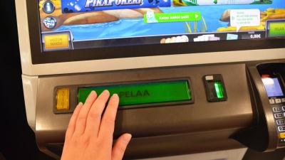 Närbild på en spelautomat och en hand som trycker på en stor knapp där det står pelaa.
