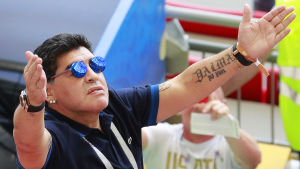 Fotbollslegenden Diego Maradona slår ut med armarna mot skyn.