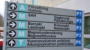 Skylt som visar riktningen till olika avdelningar på ett sjukhus.