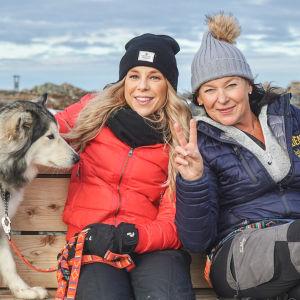 Krista och Lotta och en hund sitter på en bänk ute i Lappland.