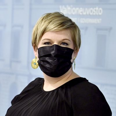 I förgrunden Annika Saarikko, i bakgrunden Antti Kurvinen. De står vid talarpodium och håller presskonferens. De har båda munskydd på sig.