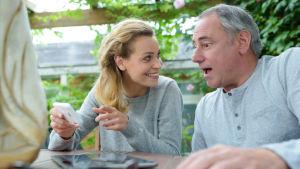 ung kvinna och äldre man tittar på telefon och skrattar
