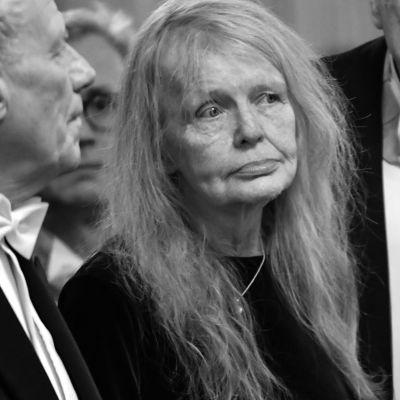 Författaren Kristina Lugn ser förbi kameran med neturalt ansiktsuttryck. Hon har långt hår och är klädd i svart.