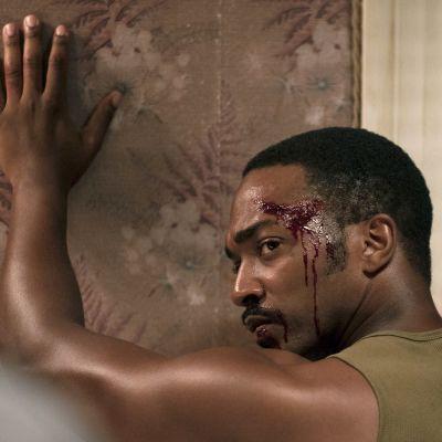 Musta mies seisoo lähikuvassa kädet ylhäällä, otsassa verta, kuva elokuvasta Detroit