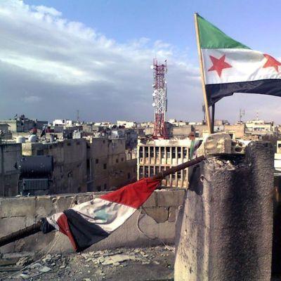 Rebellernas flagga vajar över en byggnad i Homs