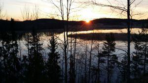 Aurinko pilkottaa järvenselän takaa.