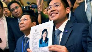 Den glädjestrålande ledaren för Thai Raksa Chart, Preechapol Pongpanich visar upp dokumentet som bevisar prinsessan Ubolratnas kandidatur.