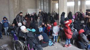 Invånare i östra Aleppo som evakuerats av regeringsstyrkor väntar på bussar mot flyktingcenter 29.11.2016