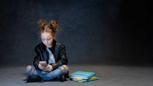 ett barn tittar på mobiltelefonen i ett mörkt rum